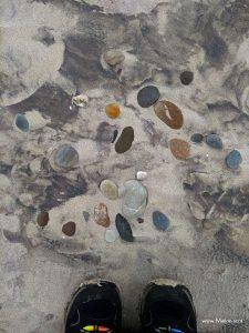 Look down pebbles on sandy beach