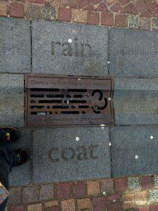 Look down rain coat word in pavement