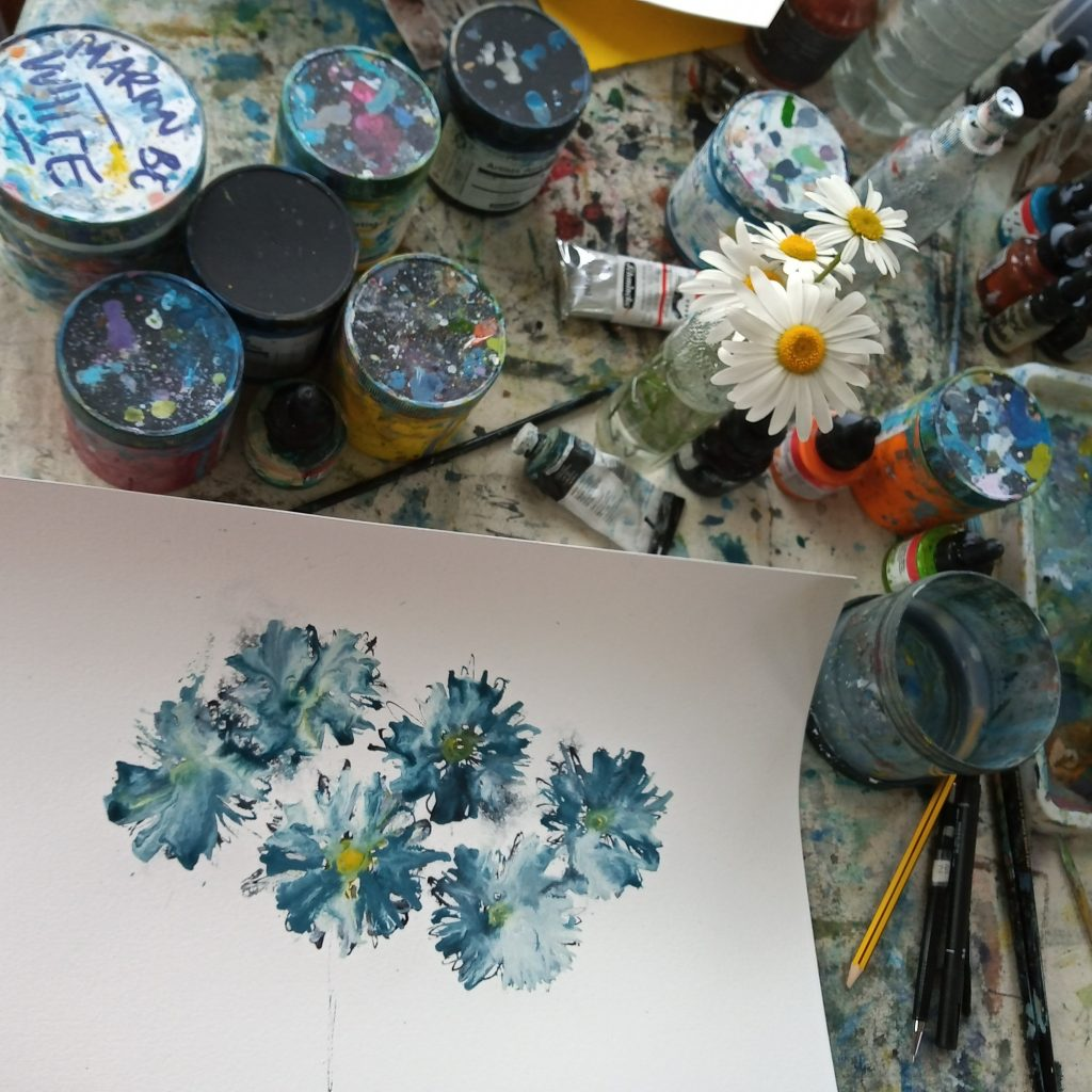 Photo of my painting table with blue and white daisies painted on paper