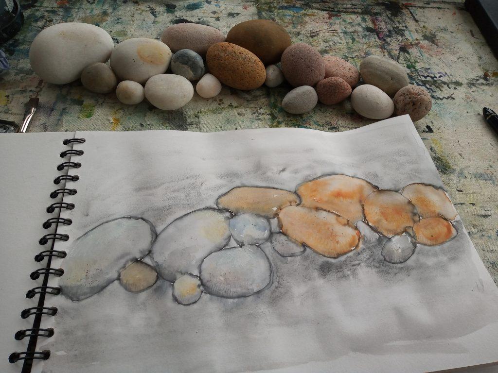 Drawing pebbles in a sketchbook